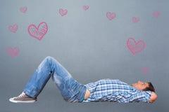 Σύνθετη εικόνα του νεαρού άνδρα που βρίσκεται στη σκέψη πατωμάτων Στοκ φωτογραφία με δικαίωμα ελεύθερης χρήσης