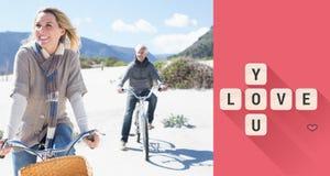 Σύνθετη εικόνα του ξένοιαστου ζεύγους που πηγαίνει σε έναν γύρο ποδηλάτων στην παραλία Στοκ Εικόνες