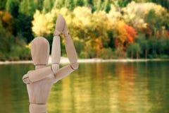 Σύνθετη εικόνα του ξύλινου ειδωλίου που στέκεται και με τα δύο χέρια που ενώνονται Στοκ Εικόνες