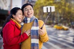 Σύνθετη εικόνα του παλαιότερου ασιατικού ζεύγους στο μπαλκόνι που παίρνει selfie Στοκ φωτογραφία με δικαίωμα ελεύθερης χρήσης