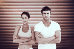 Σύνθετη εικόνα του πορτρέτου ενός κατάλληλου νέου ζεύγους με τα όπλα που διασχίζονται Στοκ φωτογραφία με δικαίωμα ελεύθερης χρήσης