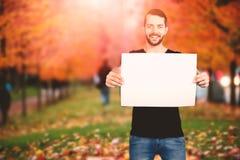Σύνθετη εικόνα του πορτρέτου του ευτυχούς ατόμου που παρουσιάζει κενό χαρτόνι Στοκ Εικόνες