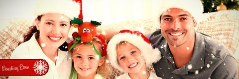 Σύνθετη εικόνα του πορτρέτου μιας ευτυχούς οικογένειας με τα καπέλα Χριστουγέννων που κάθεται στον καναπέ στοκ φωτογραφία με δικαίωμα ελεύθερης χρήσης