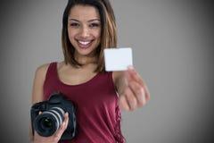 Σύνθετη εικόνα του πορτρέτου της ευτυχούς γυναίκας που παρουσιάζει δελτίο ταυτότητας κρατώντας τη κάμερα Στοκ φωτογραφία με δικαίωμα ελεύθερης χρήσης