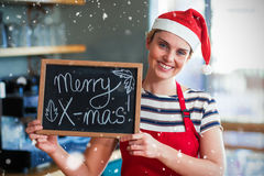Σύνθετη εικόνα του πορτρέτου της σερβιτόρας που παρουσιάζει πλάκα με το εύθυμο σημάδι Χριστουγέννων Στοκ Φωτογραφίες