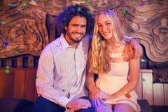 Σύνθετη εικόνα του πορτρέτου της συνεδρίασης ζευγών μαζί στο φραγμό στοκ φωτογραφία με δικαίωμα ελεύθερης χρήσης
