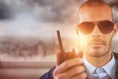 Σύνθετη εικόνα του πορτρέτου του αξιωματικού ασφαλείας που μιλά στην ομιλούσα ταινία walkie Στοκ Φωτογραφία