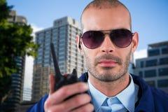 Σύνθετη εικόνα του πορτρέτου του αξιωματικού ασφαλείας που μιλά στην ομιλούσα ταινία walkie Στοκ Εικόνες