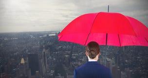 Σύνθετη εικόνα του πλήρους μήκους οπισθοσκόπος της επιχειρηματία που φέρνει την κόκκινους ομπρέλα και το χαρτοφύλακα στοκ φωτογραφίες