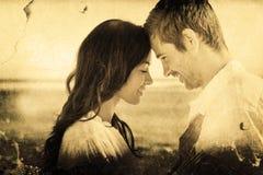 Σύνθετη εικόνα του ρομαντικού ζεύγους που χαλαρώνει και που αγκαλιάζει στην παραλία Στοκ Εικόνες
