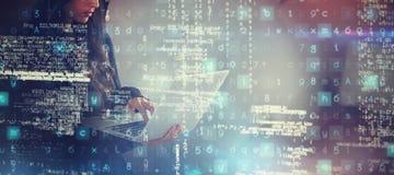 Σύνθετη εικόνα του σοβαρού θηλυκού χάκερ που χρησιμοποιεί το lap-top στεμένος Στοκ εικόνα με δικαίωμα ελεύθερης χρήσης