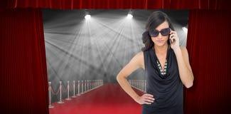 Σύνθετη εικόνα του σοβαρού κομψού brunette που φορά τα γυαλιά ηλίου στο τηλέφωνο Στοκ Εικόνες