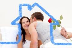 Σύνθετη εικόνα του συζύγου που δίνει ένα τριαντάφυλλο και ένα φιλί στην όμορφη σύζυγό του Στοκ Εικόνα