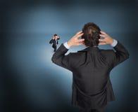 Σύνθετη εικόνα του τονισμένου επιχειρηματία με τα χέρια στο κεφάλι με το μικροσκοπικό επιχειρηματία Στοκ Εικόνα
