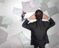 Σύνθετη εικόνα του τονισμένου επιχειρηματία με τα χέρια στο κεφάλι με το μικροσκοπικό επιχειρηματία Στοκ Φωτογραφία