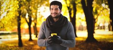 Σύνθετη εικόνα του χαμογελώντας ατόμου που κοιτάζει μακριά κρατώντας την κούπα του καφέ Στοκ εικόνες με δικαίωμα ελεύθερης χρήσης