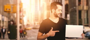 Σύνθετη εικόνα του χαμογελώντας νεαρού άνδρα που δείχνει προς το κενό χαρτόνι Στοκ Φωτογραφία