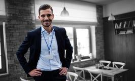 Σύνθετη εικόνα του χαμογελώντας επιχειρηματία με το χέρι στο ισχίο που φορά την ταυτότητα στοκ εικόνα με δικαίωμα ελεύθερης χρήσης