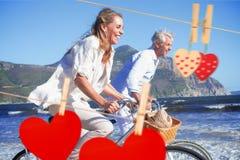 Σύνθετη εικόνα του χαμογελώντας ζεύγους που οδηγά τα ποδήλατά τους στην παραλία Στοκ φωτογραφία με δικαίωμα ελεύθερης χρήσης