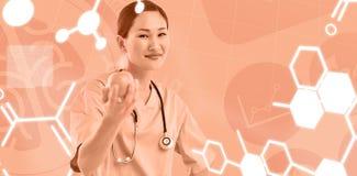 Σύνθετη εικόνα του χαμογελώντας χειρούργου που κρατά ένα μήλο με το συνάδελφο στο νοσοκομείο Στοκ Φωτογραφία