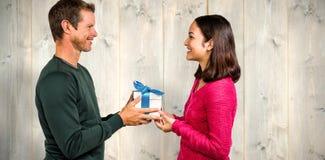 Σύνθετη εικόνα του χαμόγελου του κιβωτίου δώρων εκμετάλλευσης ζευγών Στοκ φωτογραφία με δικαίωμα ελεύθερης χρήσης
