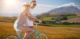 Σύνθετη εικόνα του χαριτωμένου ζεύγους σε μια ψηφιακή σύνθετη εικόνα γύρου ποδηλάτων Στοκ Εικόνες