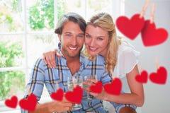 Σύνθετη εικόνα του χαριτωμένου χαμογελώντας ζεύγους που απολαμβάνει το άσπρο κρασί από κοινού Στοκ φωτογραφία με δικαίωμα ελεύθερης χρήσης