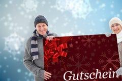 Σύνθετη εικόνα του χειμερινού ζεύγους που παρουσιάζει αφίσα Στοκ εικόνα με δικαίωμα ελεύθερης χρήσης