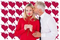 Σύνθετη εικόνα του όμορφου ατόμου που δίνει στη σύζυγό του ένα φιλί στο μάγουλο Στοκ Εικόνα