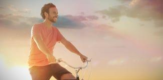 Σύνθετη εικόνα του όμορφου ατόμου σε έναν γύρο ποδηλάτων μια ηλιόλουστη ημέρα Στοκ φωτογραφία με δικαίωμα ελεύθερης χρήσης