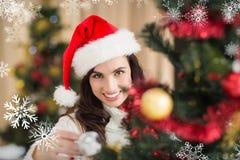 Σύνθετη εικόνα του brunette ομορφιάς που διακοσμεί ένα χριστουγεννιάτικο δέντρο Στοκ Φωτογραφίες