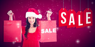 Σύνθετη εικόνα των εορταστικών τσαντών πώλησης εκμετάλλευσης brunette Στοκ Εικόνες