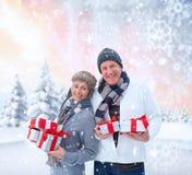 Σύνθετη εικόνα των εορταστικών ώριμων δώρων Χριστουγέννων εκμετάλλευσης ζευγών Στοκ φωτογραφία με δικαίωμα ελεύθερης χρήσης