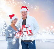Σύνθετη εικόνα των εορταστικών ώριμων δώρων Χριστουγέννων εκμετάλλευσης ζευγών Στοκ Εικόνα