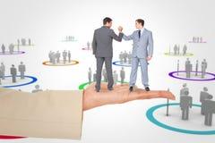 Σύνθετη εικόνα των επιχειρηματιών που τινάζουν τα χέρια στοκ εικόνα