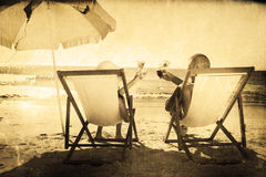 Σύνθετη εικόνα των ευτυχών κοκτέιλ κατανάλωσης ζευγών χαλαρώνοντας στις καρέκλες γεφυρών τους Στοκ φωτογραφίες με δικαίωμα ελεύθερης χρήσης