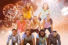 Σύνθετη εικόνα των ευτυχών φίλων που κάνουν την ανθρώπινη πυραμίδα στοκ φωτογραφία με δικαίωμα ελεύθερης χρήσης