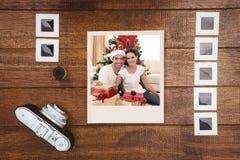 Σύνθετη εικόνα των ευτυχών Χριστουγέννων εορτασμού ζευγών στο σπίτι στοκ εικόνες