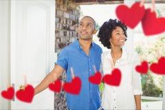 Σύνθετη εικόνα των κόκκινων κρεμώντας καρδιών και του ζεύγους που εισάγονται κατ' οίκον Στοκ Εικόνες