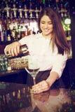 Σύνθετη εικόνα όμορφο bartender που χύνει το μπλε martini ποτό στο γυαλί Στοκ εικόνες με δικαίωμα ελεύθερης χρήσης
