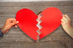 Σύνθετη εικόνα δύο χεριών που κρατά τη σπασμένη καρδιά Στοκ φωτογραφία με δικαίωμα ελεύθερης χρήσης