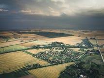 Σύννεφα θύελλας πέρα από το μικρό μακρινό χωριό στη Λιθουανία στοκ εικόνες