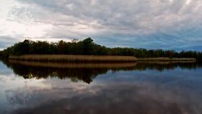 Σύννεφα θύελλας που κινούνται πέρα από τη λίμνη στο ηλιοβασίλεμα Ζωηρόχρωμος ουρανός του μπλε, κίτρινος και πορτοκαλής στην ανατο απόθεμα βίντεο