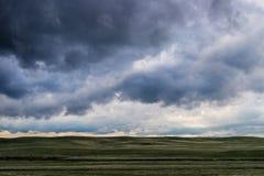 Σύννεφα θύελλας επάνω από τον τομέα της πράσινης χλόης Στοκ Εικόνες