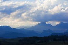 Σύννεφα και μπλε βουνά Στοκ Φωτογραφίες