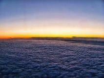 Σύννεφα και ο ωκεανός στο ηλιοβασίλεμα άνωθεν, από ένα αεροπλάνο στοκ εικόνες