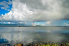 Σύννεφα πέρα από την αντανάκλαση λιμνών στο νερό και το ουράνιο τόξο Στοκ εικόνα με δικαίωμα ελεύθερης χρήσης