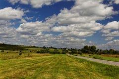 Σύννεφα πέρα από τον τομέα μια ηλιόλουστη ημέρα στοκ φωτογραφία