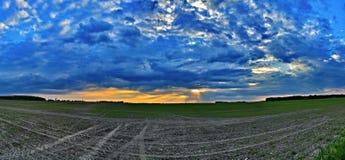Σύννεφα πέρα από τον τομέα στο ηλιοβασίλεμα στοκ εικόνες