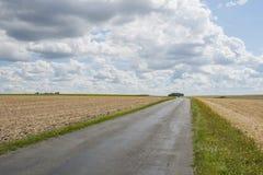 Σύννεφα πέρα από το καλλιεργήσιμο έδαφος κοντά σε Royan με τον ποδηλάτη Στοκ Εικόνα